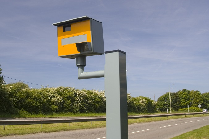 Landscape photo of road and yellow speeding camera.
